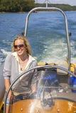 Ragazza della giovane donna in barca di potere in mare Fotografie Stock