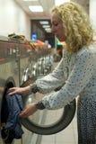 Ragazza della lavanderia automatica che inserisce i vestiti immagini stock libere da diritti