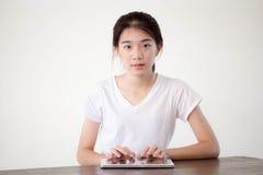 Ragazza della porcellana dell'Asia bella dell'università tailandese dello studente che per mezzo della sua compressa Fotografie Stock