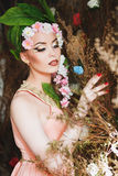 Ragazza della primavera di bellezza con i capelli dei fiori Bella donna di modello con i fiori su lei capa La natura dell'acconci Fotografia Stock