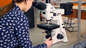 Ragazza della scuola che esamina microscopio Primo piano video d archivio