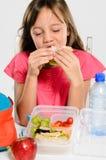 Ragazza della scuola che mangia il suo panino imballato del pranzo Fotografia Stock Libera da Diritti