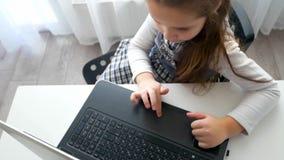 Ragazza della scuola che per mezzo del computer portatile per scrivere qualcosa a macchina video d archivio
