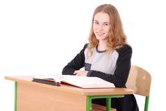 Ragazza della scuola che si siede ad uno scrittorio Fotografia Stock