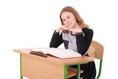 Ragazza della scuola che si siede ad uno scrittorio Immagine Stock Libera da Diritti