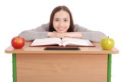 Ragazza della scuola che si siede ad uno scrittorio Immagini Stock