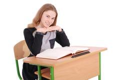 Ragazza della scuola che si siede ad uno scrittorio Fotografia Stock Libera da Diritti