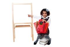 Ragazza della scuola che si siede sul mucchio dei libri Immagine Stock