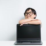 Ragazza della scuola con il pensiero del computer portatile Fotografie Stock Libere da Diritti