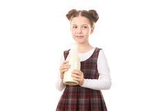 Ragazza della scuola con la bottiglia per il latte Fotografie Stock Libere da Diritti
