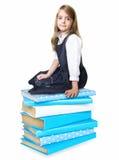 Ragazza della scuola del bambino che si siede sul mucchio della pila dei libri isolati Immagine Stock