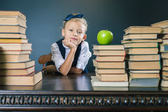 Ragazza della scuola del primo piano che si siede alla tavola con molti libri Immagini Stock