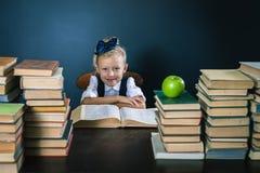 Ragazza della scuola del primo piano che si siede alla tavola con molti libri Fotografie Stock Libere da Diritti