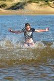 Ragazza della spiaggia nell'azione fotografia stock
