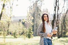 Ragazza della studentessa fuori con le cuffie che camminano con i taccuini in parco Immagine Stock