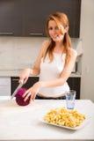 Ragazza della testarossa che affetta nella cucina Fotografia Stock Libera da Diritti