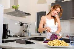 Ragazza della testarossa che affetta nella telefonata della cucina fotografia stock