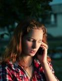 Ragazza della testarossa che chiama dal telefono cellulare Fotografie Stock Libere da Diritti