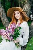Ragazza della testarossa con un mazzo dei lillà in un giardino della molla Immagini Stock Libere da Diritti