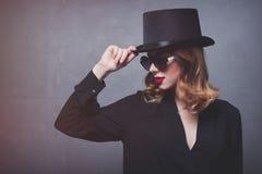 Ragazza della testarossa di mistica e di stile in cilindro ed occhiali da sole Fotografia Stock