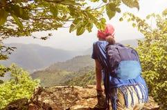 Ragazza della viandante che guarda giù dall'alta scogliera Fotografie Stock