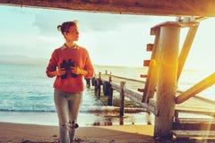 Ragazza della viandante con il binocolo a disposizione che fa una pausa il mare vicino al pilastro fotografia stock