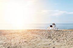 Ragazza delle free lance che lavora alla vacanza, davanti al bello mare, sedentesi con un computer portatile sull'oceano, posto i fotografia stock libera da diritti