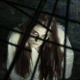 Ragazza delle zombie dietro grata immagine stock