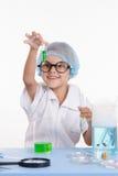 Ragazza dello scienziato che esamina felicemente la provetta con liquido Immagini Stock