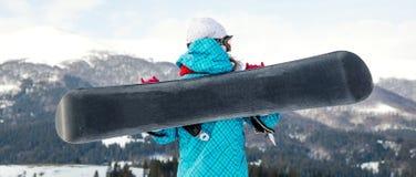 Ragazza dello Snowboarder che sta con lo snowboard, Fotografie Stock