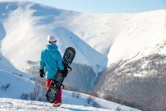 Ragazza dello Snowboarder che sta con lo snowboard, Immagini Stock