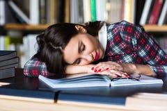 Ragazza dello studente che dorme nella biblioteca Immagine Stock