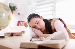 Ragazza dello studente che dorme sopra i libri allo scrittorio Fotografie Stock Libere da Diritti