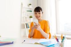 Ragazza dello studente che impara e che per mezzo dello smartphone a casa Immagini Stock