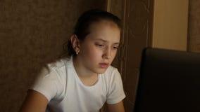 Ragazza dello studente che lavora al computer portatile a casa nella sala alla notte impianti stanchi della ragazza al computer archivi video