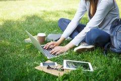Ragazza dello studente che lavora con il computer portatile nel parco durante il giorno Immagini Stock