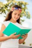 Ragazza dello studente che legge un libro all'aperto Fotografia Stock