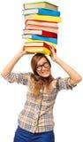Ragazza dello studente che lotta con la pila di libri Fotografie Stock