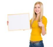 Ragazza dello studente che mostra bordo ed i pollici in bianco su Fotografia Stock