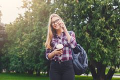 Ragazza dello studente che parla sul cellulare con la tazza di caffè Fotografia Stock