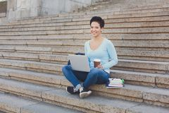 Ragazza dello studente che si siede sulle scale con caffè ed il computer portatile all'aperto Immagine Stock