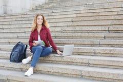 Ragazza dello studente che si siede sulle scale, leggente le note e per mezzo del computer portatile all'aperto Immagini Stock