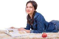 Ragazza dello studente che si trova sul tappeto e sul libro di lettura Immagine Stock