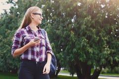 Ragazza dello studente che sta con il telefono cellulare all'aperto Fotografia Stock Libera da Diritti