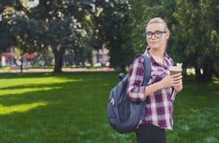 Ragazza dello studente che sta con la tazza di caffè all'aperto Immagini Stock