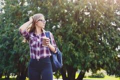 Ragazza dello studente che sta con la tazza di caffè all'aperto Fotografia Stock