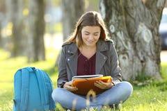 Ragazza dello studente che studia le note della lettura all'aperto Fotografie Stock