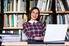Ragazza dello studente con funzionamento di vetro su un computer portatile nella biblioteca ragazza dello studente che lavora ad  Fotografia Stock