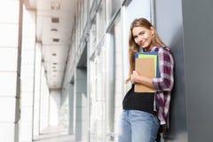 Ragazza dello studente con i libri sul fondo di università Immagine Stock Libera da Diritti