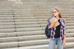 Ragazza dello studente con i libri sul fondo di università Fotografie Stock Libere da Diritti